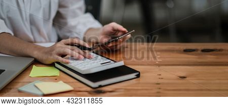 Close Up Hand Of Accounant Or Bookkeeper Using Calculator And Mobile Phone, Calculating Financial Ex
