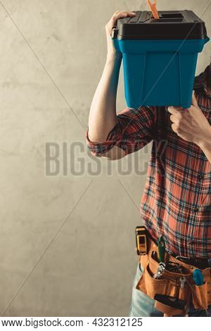 Worker man holding construction toolbox near wall. Male hand and construction tools for house room renovation. Home renovation concept