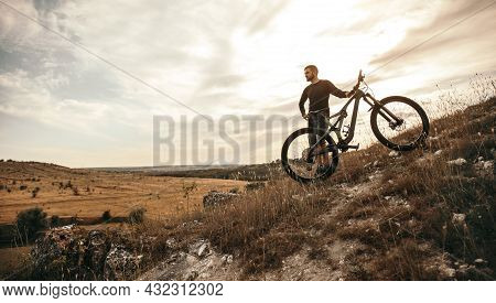 Full Body Of Active Male Cyclist In Sportswear Standing Near Electric Gravel Bike And Contemplating