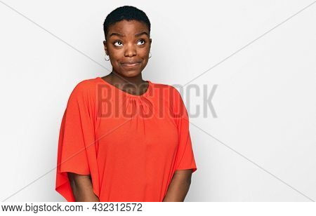Young african american woman wearing casual clothes smiling looking to the side and staring away thinking.