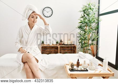 Young blonde woman wearing bathrobe at wellbeing spa very happy and smiling looking far away with hand over head. searching concept.
