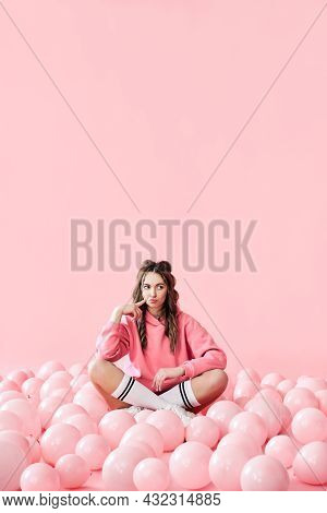 Young Thoughtful Woman Sitting On Floor With Pink Balloons On Pink Pastel Background