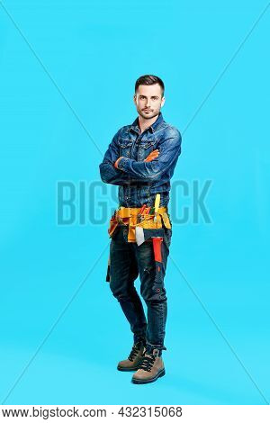 Full Length Portrait Of Confident Handsome Male Construction Worker Staying Over Blue Background