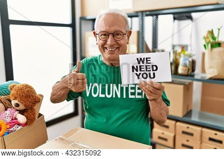 Senior volunteer man holding we need you banner smiling happy and positive, thumb up doing excellent and approval sign