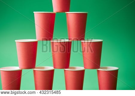 Pyramid Of Pink Paper Cups On Green Background.
