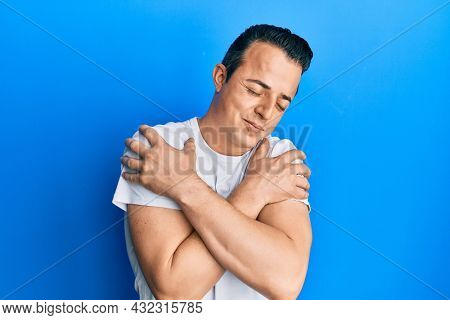 Handsome young man wearing casual white t shirt hugging oneself happy and positive, smiling confident. self love and self care