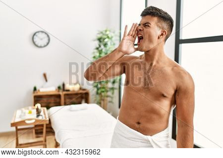 Young hispanic man standing shirtless at spa center shouting and screaming loud to side with hand on mouth. communication concept.