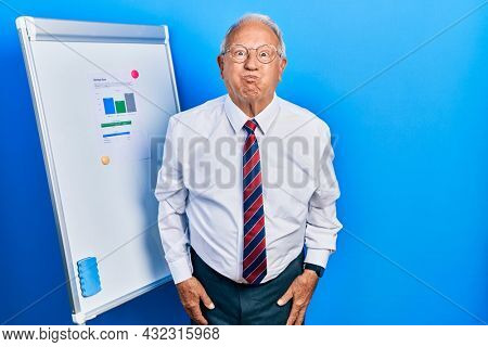 Senior man with grey hair standing by business blackboard puffing cheeks with funny face. mouth inflated with air, crazy expression.