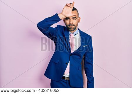 Young hispanic man wearing business suit and tie making fun of people with fingers on forehead doing loser gesture mocking and insulting.