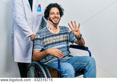 Handsome hispanic man sitting on wheelchair wearing neck collar showing and pointing up with fingers number four while smiling confident and happy.
