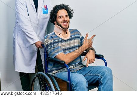 Handsome hispanic man sitting on wheelchair wearing neck collar cheerful with a smile of face pointing with hand and finger up to the side with happy and natural expression on face