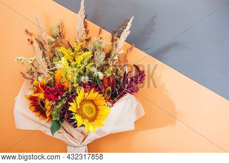 Fall Bouquet Of Yellow Red Orange Flowers Wrapped In Paper And Arranged On Brown Background. Sunflow