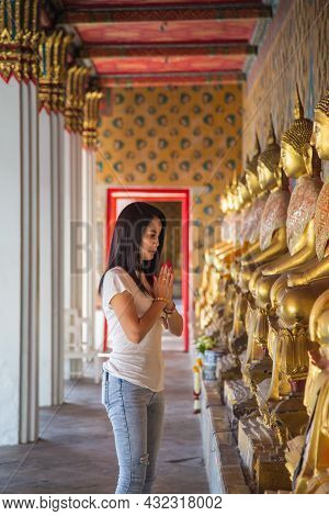 Asian Woman In A White T-shirt To Pay Respect To Buddha Statue In The Buddhist Temple While Travelin