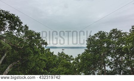The Surface Of The Ocean Is Calm. A Lone Ship Is Floating On The Water. The Sky Is Cloudy. In The Fo