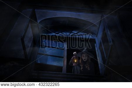 Halloween Witch Holding Ancient Lamp Standing In Old Ancient Window Castle, Halloween Mystery Concep