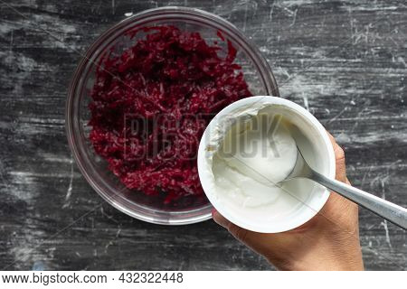 Top View Of Grated Cooked Beet In Glass Bowl And Woman Hand Holding Jar With Sour Cream On Black Bac