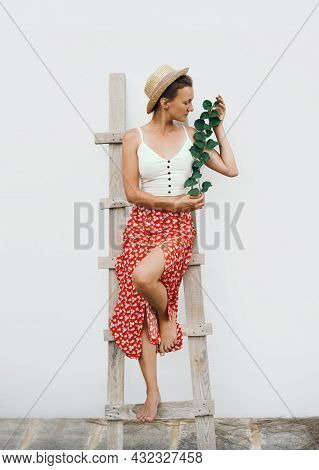 Rustic Slow Fashion Look Female With Green Plant. Elegant Style Beautiful Young Woman Against White