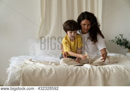 Caring Mother Reading Book Together With Small Son. Mom And Kid Bonding In Bedroom Sit In Pajamas On