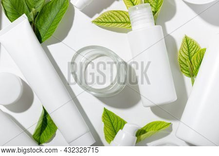 A Set Of Cosmetic Products In White Tubes And With Green Leaves With Empty Space For Labeling. Natur