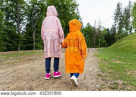 Pair Of Cute Little Caucasian Sibling Kids In Bright Waterproof Raincoats Walking Under Rain In Scen