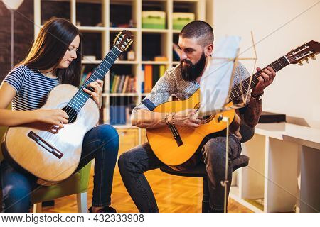 Music Teacher Tutoring Young Girl To Play Guitar At Home