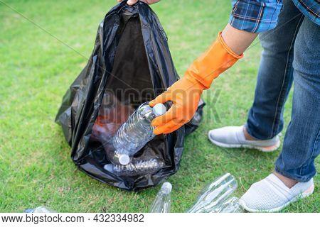 Asian Woman Volunteer Carry Water Plastic Bottles Into Garbage Bag Trash In Park, Recycle Waste Envi