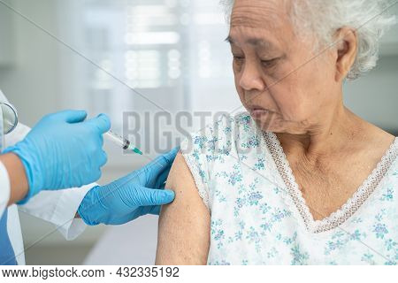 Elderly Asian Senior Woman Wearing Face Mask Getting Covid-19 Or Coronavirus Vaccine By Doctor Make