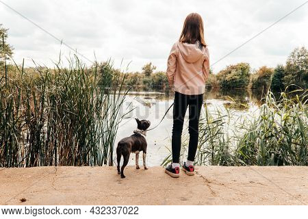 Little Girl Walking With A Boston Terrier Dog On The Lakeshore - With Her Back Turned, Her Dog Stari
