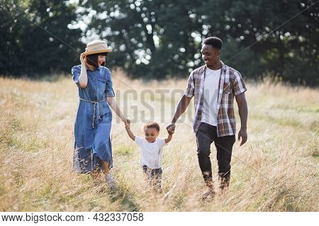 Beautiful And Happy Multiracial Family Walking On Wild Field During Warm Summer Day. Young Mother An