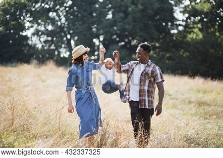 Happy Multi Ethnic Parents Playing With Son While Raising Him By Arms Outdoors. Caucasian Woman And