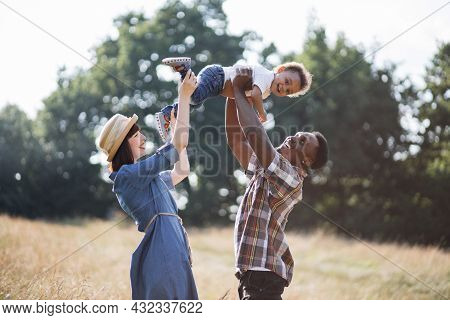 Happy Multiracial Parents Lifting Little Son While Playing On Summer Nature. Beautiful Family Of Thr