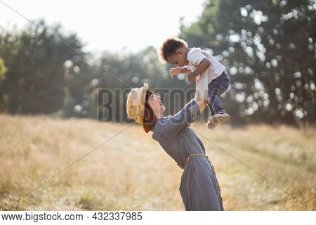 Happy Caucasian Mother In Denim Dress And Straw Hat Playing With Her African Son On Fresh Air. Multi