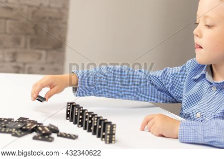 Six Year Old Cute Boy Plays Dominoes At Home On A White Wooden Table. Selective Focus. Close-up