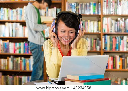 Student - Young woman in library with laptop and headphones learning, a male student standing in the Background reads a book
