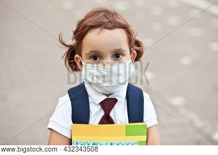 Concept Of Coronavirus Covid-19. Schoolgirl Wearing Medical Face Mask To Health Protection From Infl