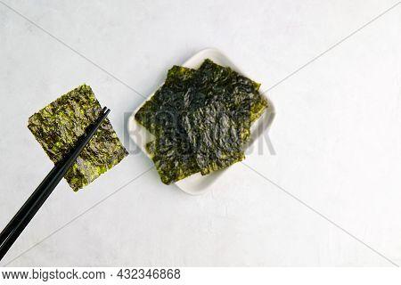 Chopsticks Hold A Piece Of Crispy Dried Seaweed. Nori, Japanese Edible Seaweed, Healthy Snack.
