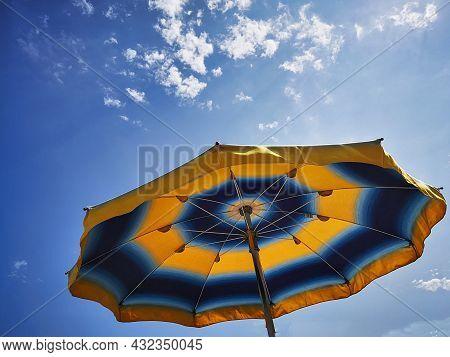 Colorful Umbrella On A Ligurian Beach In Late Summer