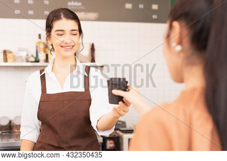 Beautiful Caucasian Barista Woman Happy To Give Takeaway Coffee Cup To Customer And Looking At Coffe