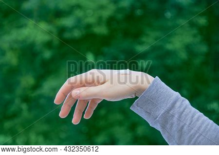 A Drop Of Hand Cream On The Hand Of A Caucasian Woman Against A Background Of Green Foliage. Natural