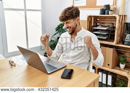 Young arab man working using computer laptop at the office very happy and excited doing winner gesture with arms raised, smiling and screaming for success. celebration concept.