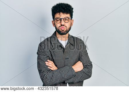 Young arab man with beard wearing glasses with arms crossed gesture puffing cheeks with funny face. mouth inflated with air, catching air.