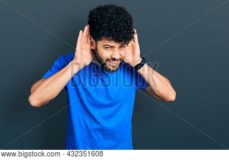 Young arab man with beard wearing casual blue t shirt trying to hear both hands on ear gesture, curious for gossip. hearing problem, deaf
