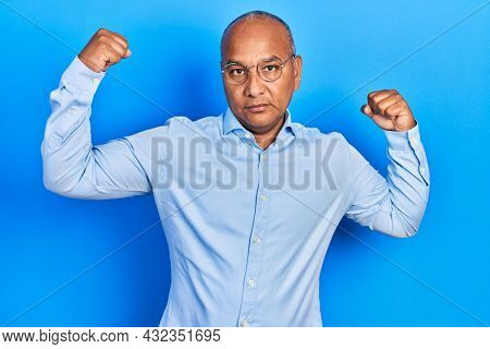 Middle age latin man wearing casual clothes and glasses showing arms muscles smiling proud. fitness concept.