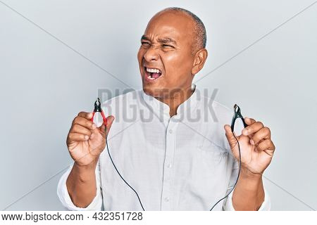 Middle age latin man holding battery charge clippers angry and mad screaming frustrated and furious, shouting with anger. rage and aggressive concept.