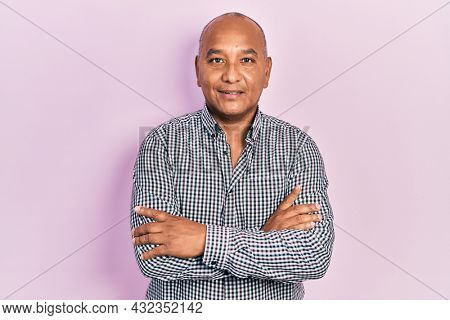 Middle age latin man wearing casual clothes happy face smiling with crossed arms looking at the camera. positive person.