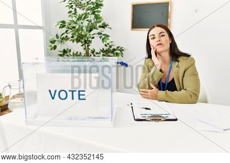 Young brunette woman sitting at election table with voting ballot thinking looking tired and bored with depression problems with crossed arms.