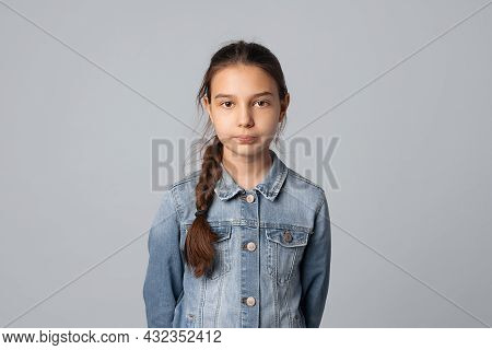 Portrait Of Smiling Preteen Girl Looking At Camera With Happy Facial Expression, Isolated On Grey Ba