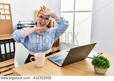 Young redhead woman working at the office using computer laptop smiling cheerful playing peek a boo with hands showing face. surprised and exited