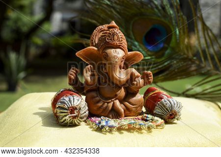 Beautiful Lord Ganesha Idol Worshipped During Ganesh Chaturthi Festival With Peacock Feather In Back