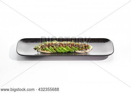 Avocado carpaccio green salad on white background. Healthy organic vegan food. Ketogenic diet. Appetizers avocado slices with unagi sauce and peanut. Trend dish in restaurant menu